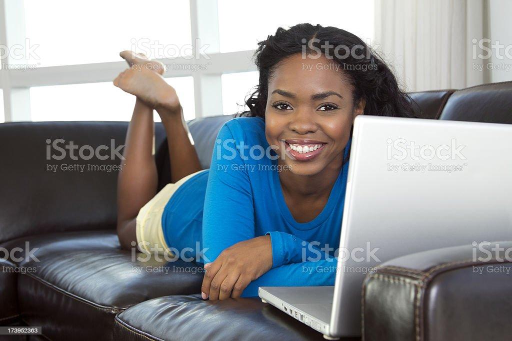 African-americanon female on sofa using laptop stock photo
