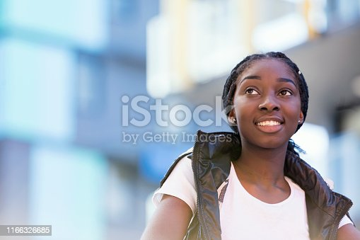 Portrait Of African-Australian Teenage Girl In Colourful Urban Location With Soft Background of Apartments