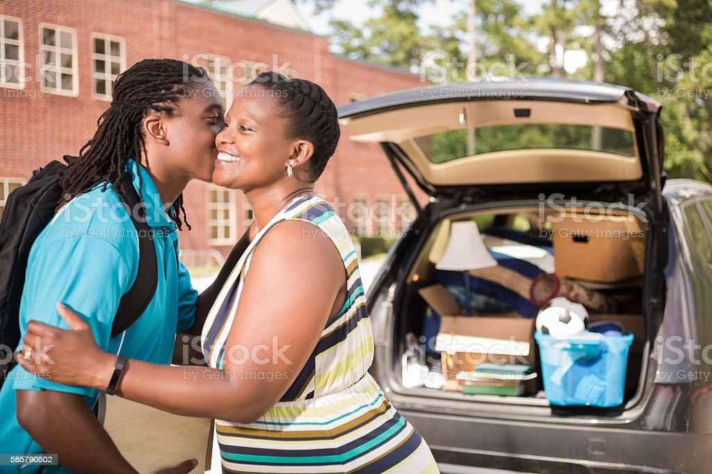 African-descent boy moves into college and kisses mom goodbye. stock photo