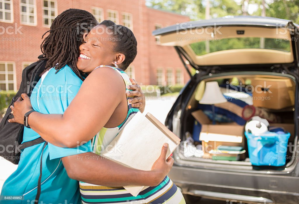 African-descent boy moves into college. Packed car, mother. School campus. stock photo