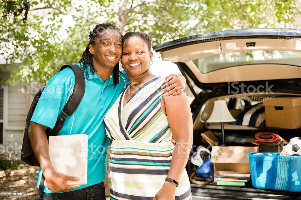 African-descent boy moves off to college.  Packed car, mom. Home. stock photo