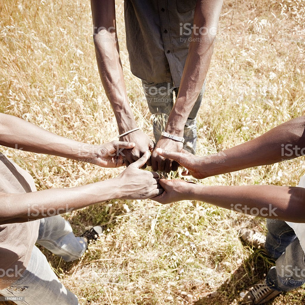 Three Africans men holding the hands of each other.