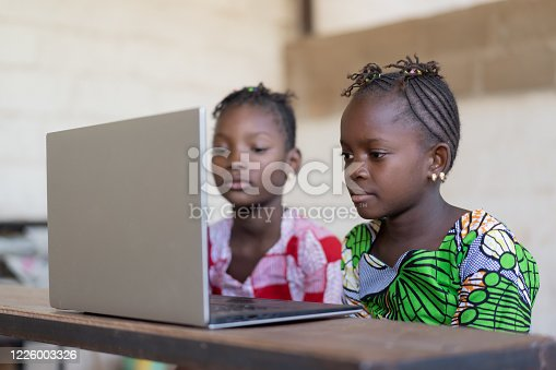 Africa's future is female: Beautiful Girls Technology Symbol. Candid picture of African children in a School Building.