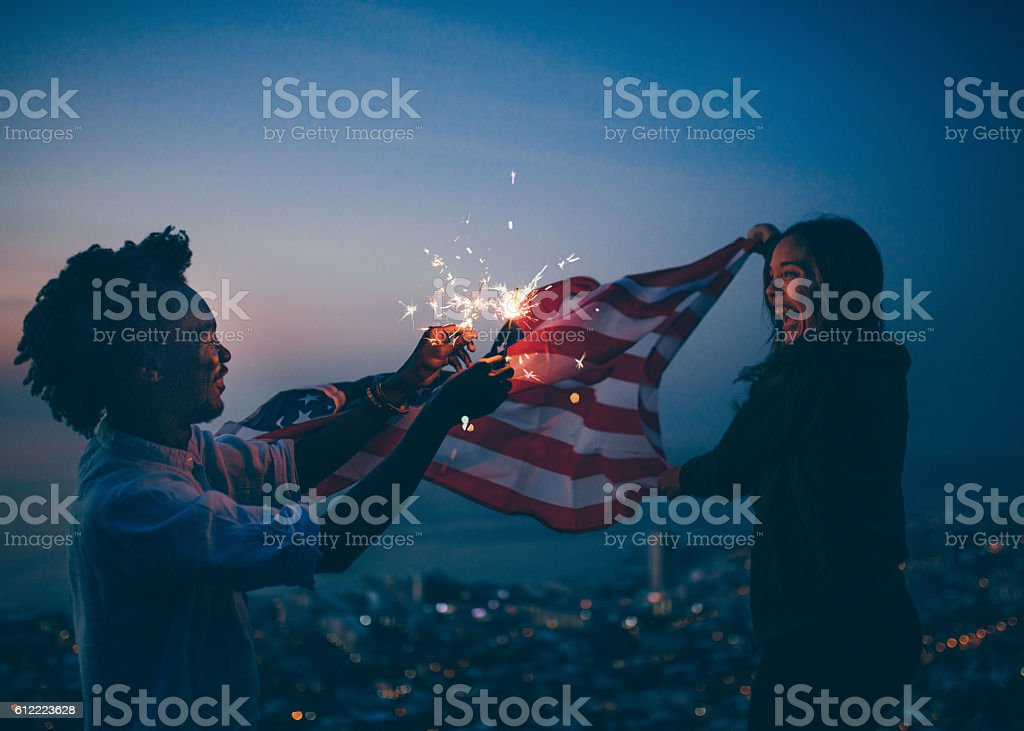 Afro amercian man and woman celebrating with USA flag and stock photo