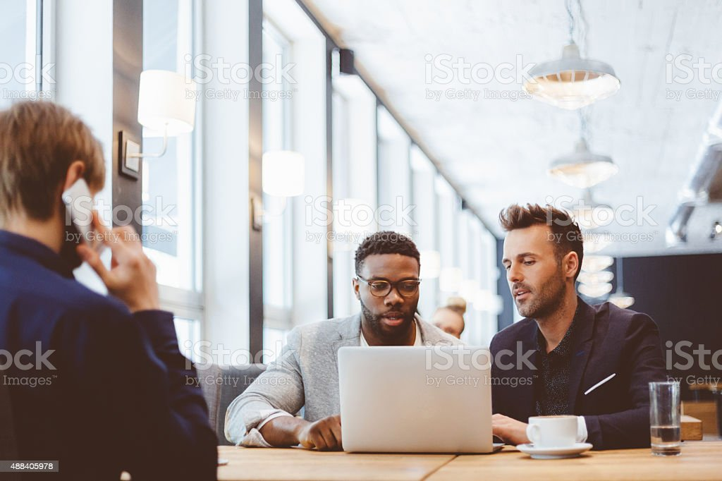 Afro american and caucasian men using laptop in the pub royalty-free stock photo