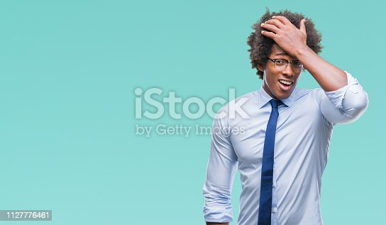 1046559700istockphoto Afro american business man wearing glasses over isolated background surprised with hand on head for mistake, remember error. Forgot, bad memory concept. 1127776461