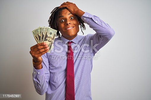 Afro american businessman with dreadlocks holding dollars over isolated white background stressed with hand on head, shocked with shame and surprise face, angry and frustrated. Fear and upset for mistake.