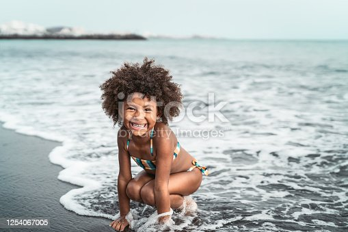 Afro American child having fun on the beach - Little kid playing during summer time outdoor - Black people and vacation concept