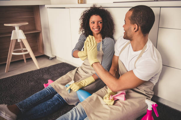 Afro American couple cleaning Beautiful young Afro American couple is giving high five and smiling while sitting on the floor in kitchen after cleaning it chores stock pictures, royalty-free photos & images