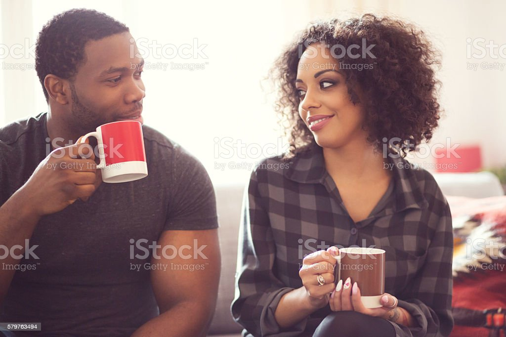 Afro american couple drinking coffee at home Afro american friendly couple sitting on sofa at home, drinking coffee, talking together. Adult Stock Photo