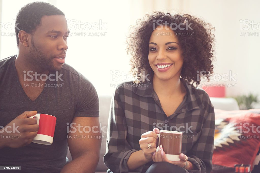 Afro american couple drinking coffee at home Afro american friendly couple sitting on sofa at home, drinking coffee, talking together. Beautiful woman smiling at camera. Adult Stock Photo