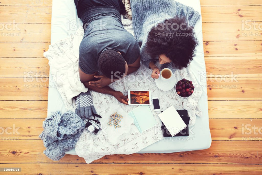 Afro american couple lying on bed and using digital tablet royalty-free stock photo