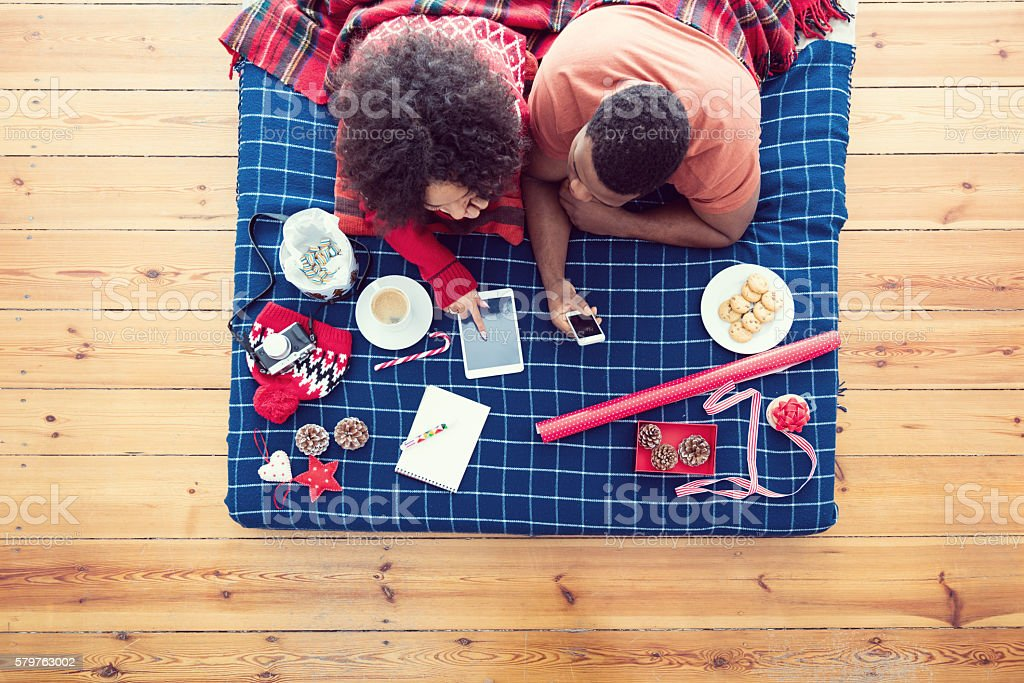 Afro american couple lying on bed and using technologies High angle view of afro american woman and man lying on the bellies on a bed and using a digital tablet and smart phone. Winter scenery. Adult Stock Photo