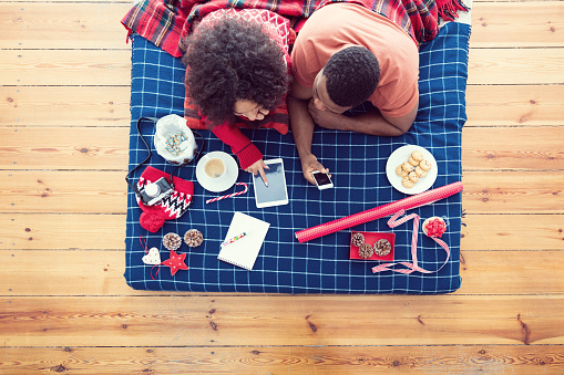Afro American Couple Lying On Bed And Using Technologies Stock Photo - Download Image Now