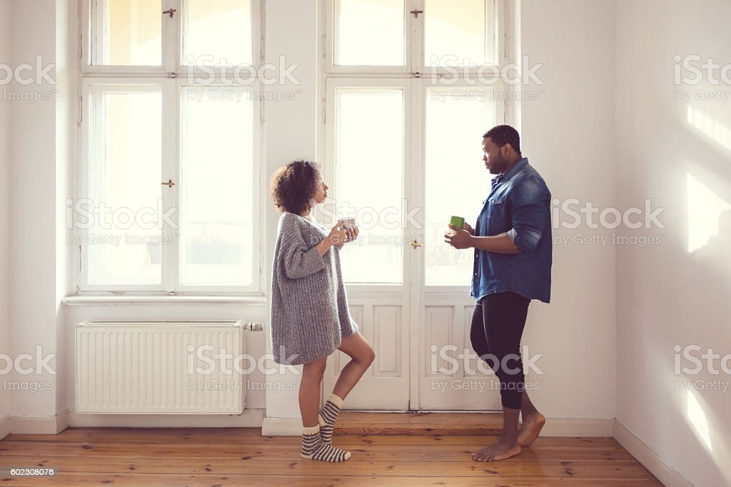 Afro american couple standing by the window at home Afro american couple talking by the window at home in the morning light, drinking coffee. Adult Stock Photo