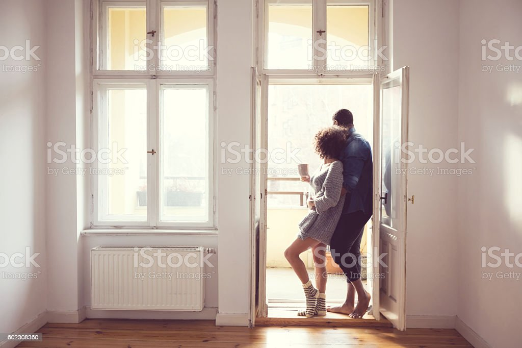 Afro american couple standing by the window at home Afro american couple embracing by the window at home in the morning light. Adult Stock Photo