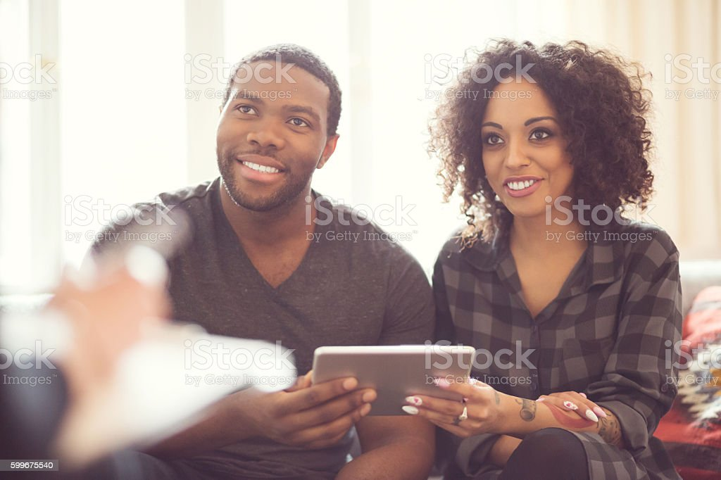 Afro american couple talking with financial advisor Afro american friendly couple sitting on sofa at home and talking with financial advisor, holding digital tabet in hands, smiling. Adult Stock Photo