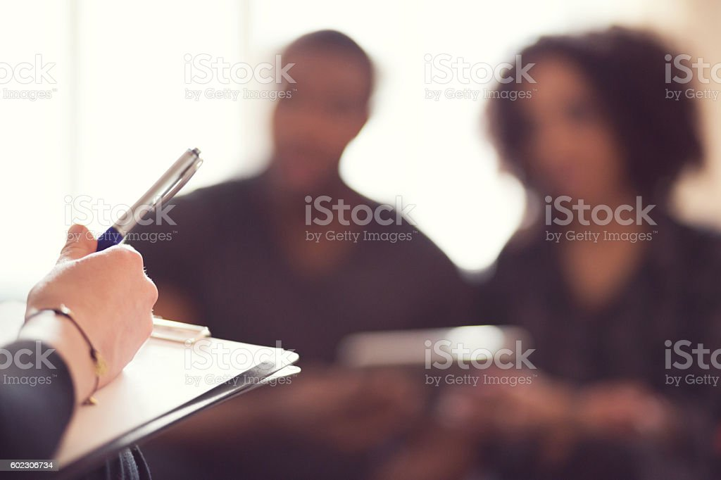 Afro american couple talking with financial advisor Afro american couple talking with financial advisor. Focus on clip board and human advisor's hand. Adult Stock Photo