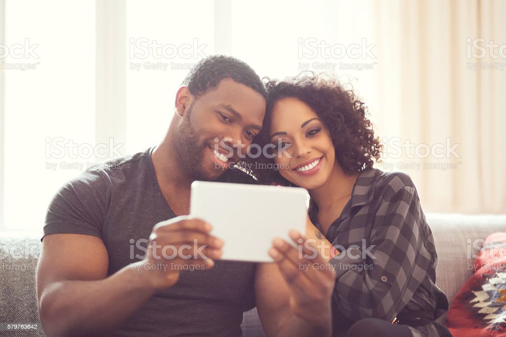 Afro american couple using a digital tablet at home Afro american friendly couple sitting on sofa at home, taking selfie using a digital tablet. Adult Stock Photo