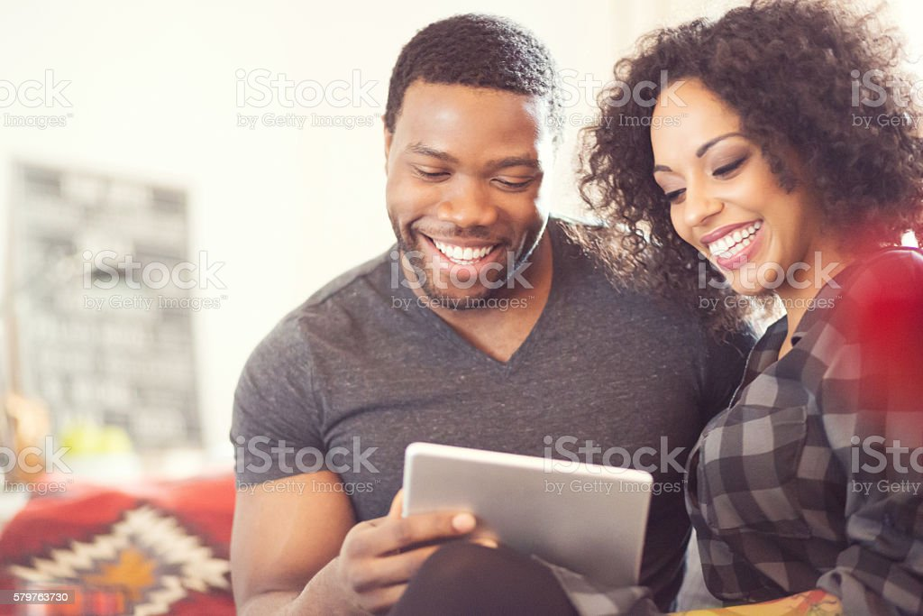 Afro american couple using a digital tablet at home Afro american friendly couple sitting on sofa at home and using a digital tablet together. Close up of faces. Adult Stock Photo