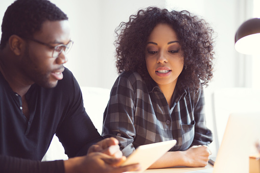 Afro American Couple Using A Digital Tablet At Home Stock Photo - Download Image Now