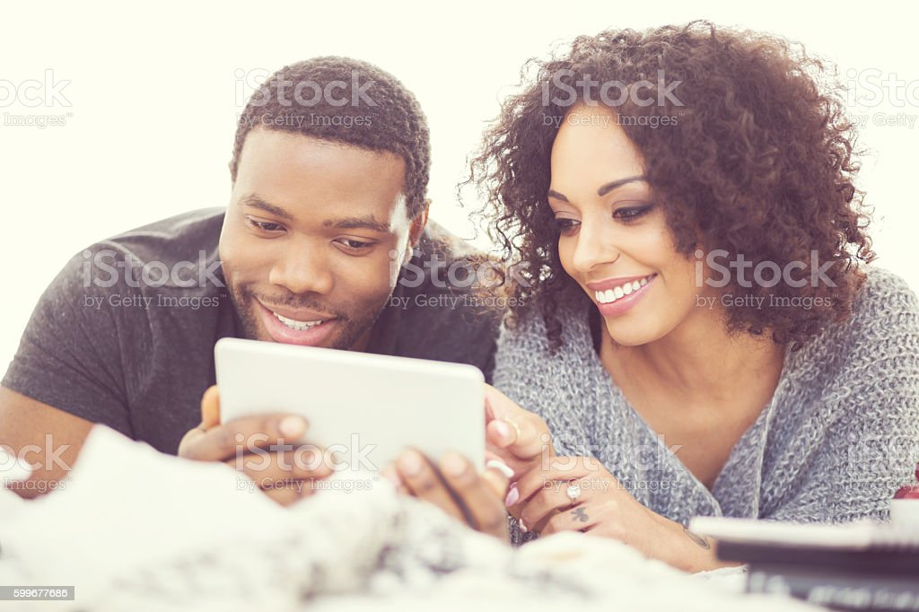 Afro american couple using a digital tablet Afro american friendly couple lying on bed at home and using a digital tablet. Close up of faces.  Adult Stock Photo