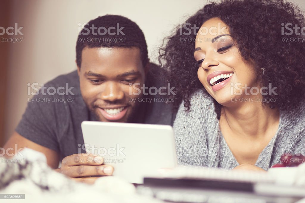Afro american couple using a digital tablet Happy afro american friendly couple lying on bed at home and using a digital tablet. Close up of faces.  Adult Stock Photo