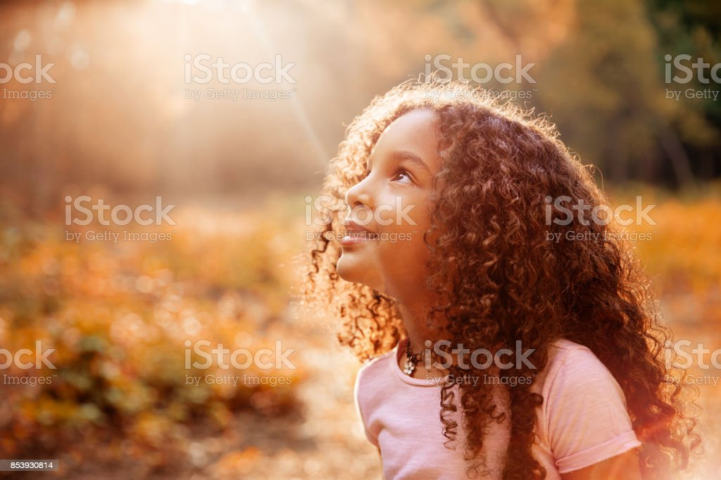 Afro american cute little girl with curly hair receives miracle sun rays from the sky stock photo