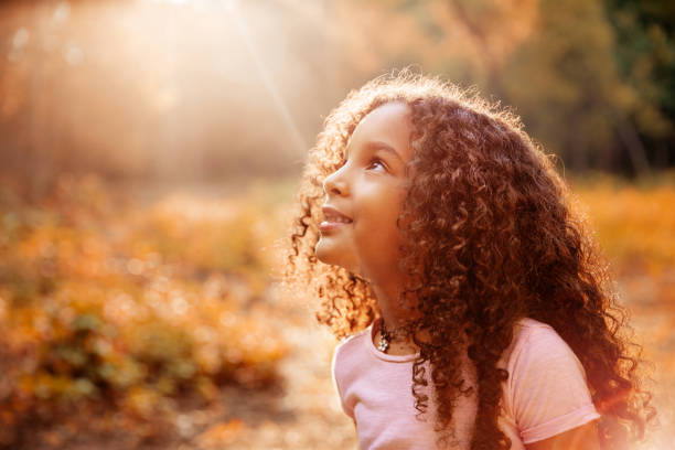 afro american cute little girl with curly hair receives miracle sun rays from the sky - religion stock pictures, royalty-free photos & images