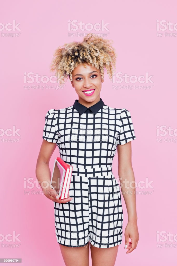 Afro american cute woman holding books Studio portrait of cute afro american young woman holding books, looking away. Pink background. 20-24 Years Stock Photo