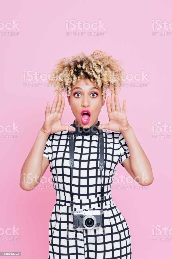 Afro american cute woman holding red heard Studio portrait of cute afro american young woman holding red heard and smiling at camera. Pink background. 20-24 Years Stock Photo
