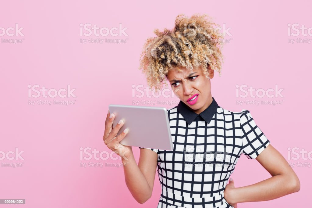 Afro american disappointed woman using a digital tablet Studio portrait of surprised afro american young woman photographing. Pink background. 20-24 Years Stock Photo