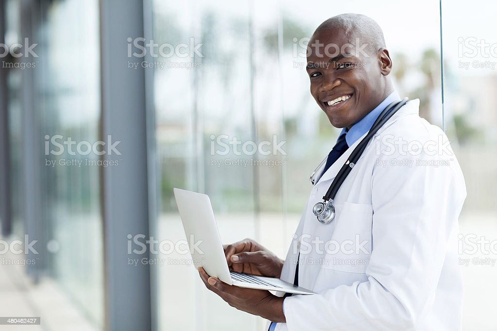 afro american doctor using laptop computer stock photo