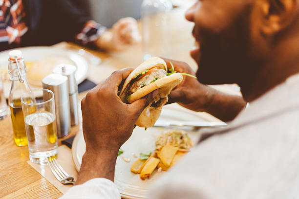 Afro américain manger le hamburger dans un restaurant - Photo