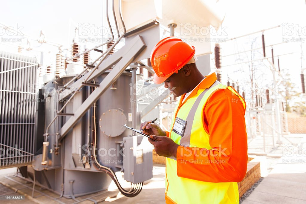 afro american electrical engineer writing on clipboard stock photo
