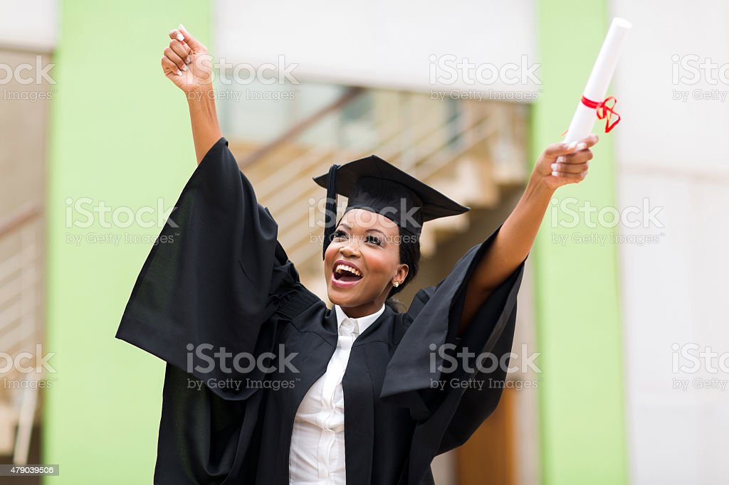 afro american female graduate standing in front of university building stock photo