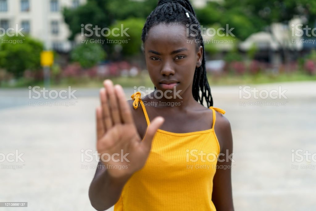 Afro american female young adult gesturing stop and distance Afro american female young adult gesturing stop and distance outdoor in summer in city Abuse Stock Photo