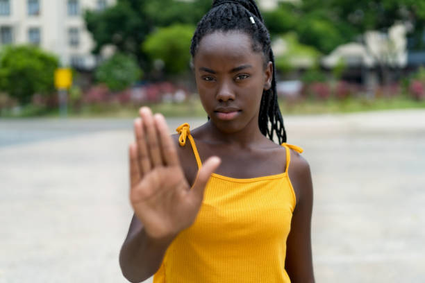 Afro american female young adult gesturing stop and distance Afro american female young adult gesturing stop and distance outdoor in summer in city prettige verrassingen stock pictures, royalty-free photos & images