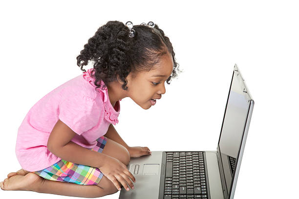 Afro American four year old girl using a laptop stock photo