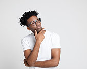 Portrait of young afro american man wearing nerd glasses looking away at copy space and thinking on white background.