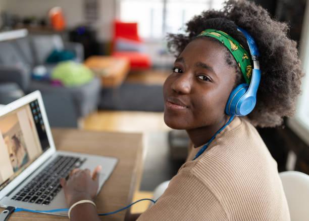 非裔美國女孩使用筆記型電腦與她的朋友聯繫 - 少女 個照片及圖片檔