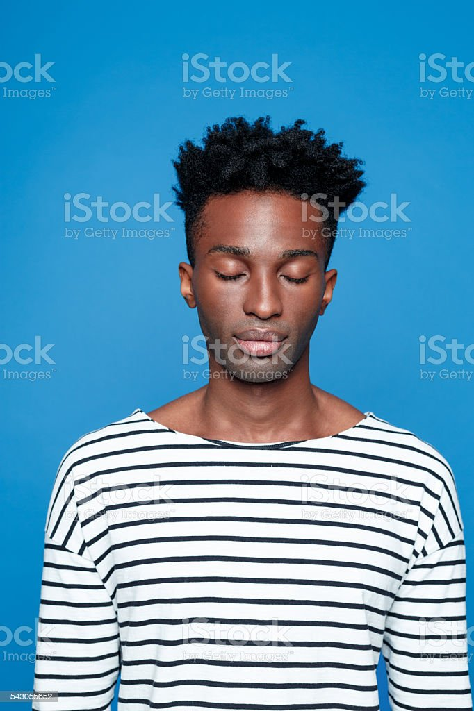 Afro american guy closing eyes Portrait of serious afro american young man wearing striped top, closing eyes. Studio portrait, blue background. Adult Stock Photo
