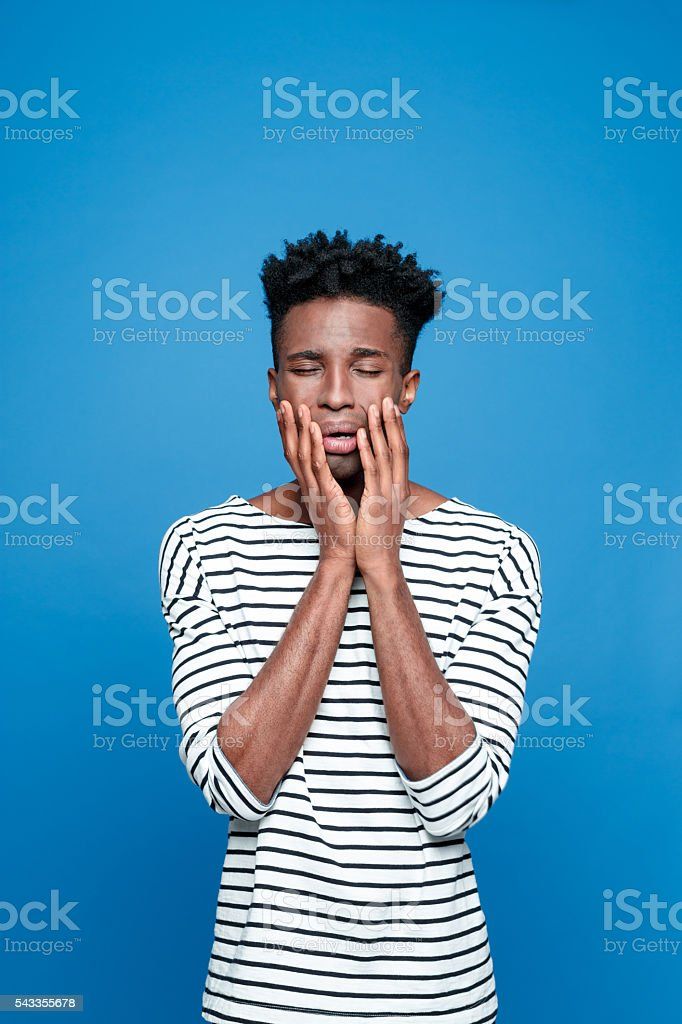 Afro american guy crying Portrait of worried afro american young man wearing striped top, crying. Studio portrait, blue background. Adult Stock Photo
