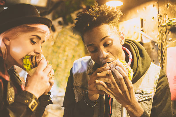 Afro american guy eating burger with his female friend - Photo