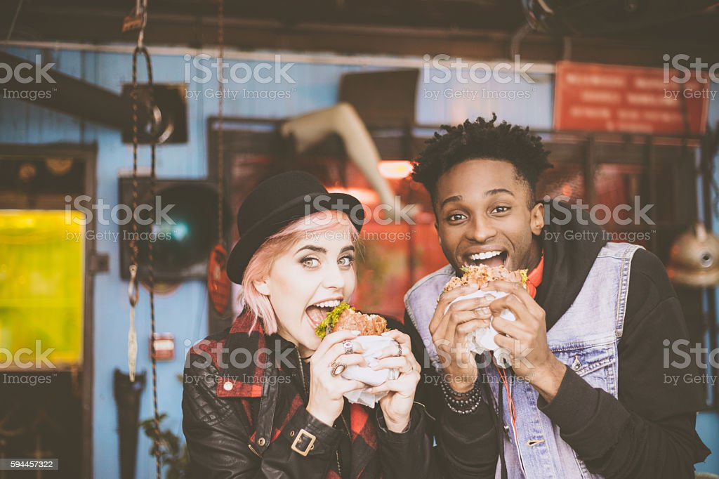 Afro american guy eating burger with his female friend stock photo