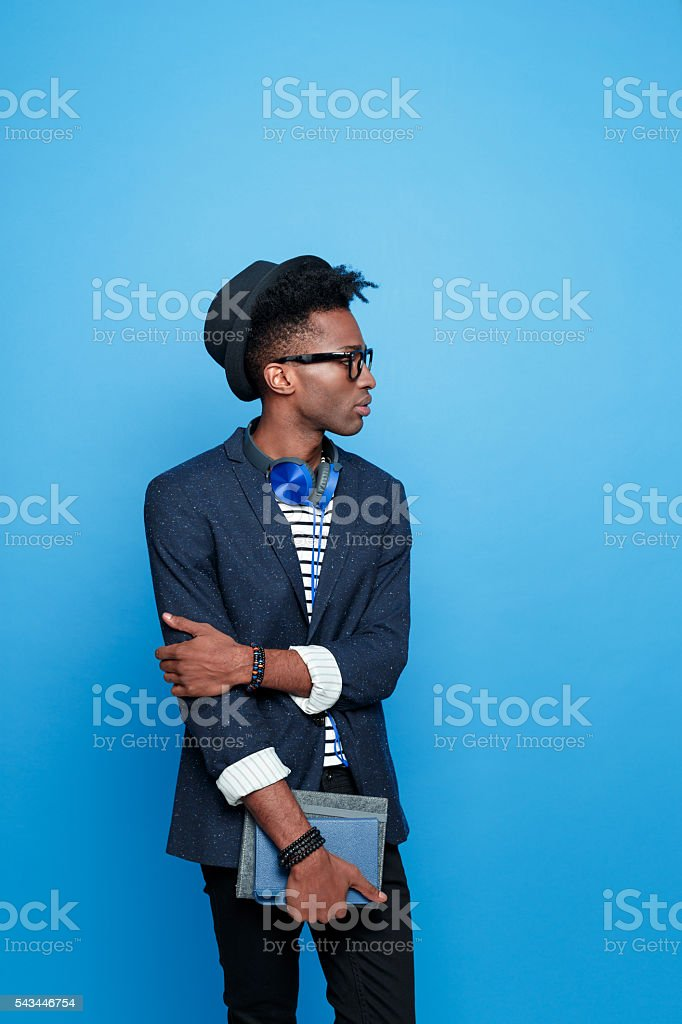 Afro american guy in fashionable outfit, holding notebook Studio portrait of afro american young man wearing striped top, navy blue jacket, hat, nerd glasses and headphone, holding a notebook in hand. Studio portrait, blue background. Adult Stock Photo