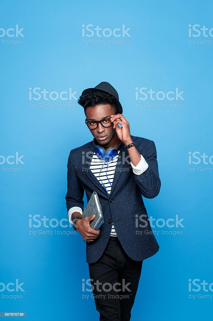 Afro american guy in fashionable outfit, holding notebook Studio portrait of afro american young man wearing striped top, navy blue jacket, hat, nerd glasses and headphone, looking at camera, holding a notebook in hand. Studio portrait, blue background. Adult Stock Photo