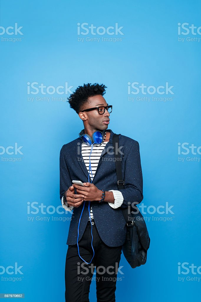 Afro american guy in fashionable outfit, holding smart phone Studio portrait of afro american young man wearing striped top, navy blue jacket, hat, nerd glasses and headphone, holding a mobile phone in hands. Studio portrait, blue background. Adult Stock Photo