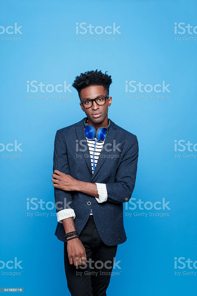Afro american guy in fashionable outfit Fashionable afro american young man wearing striped top, navy blue jacket, nerd glasses and headphone, looking at camera. Studio portrait, blue background. Adult Stock Photo