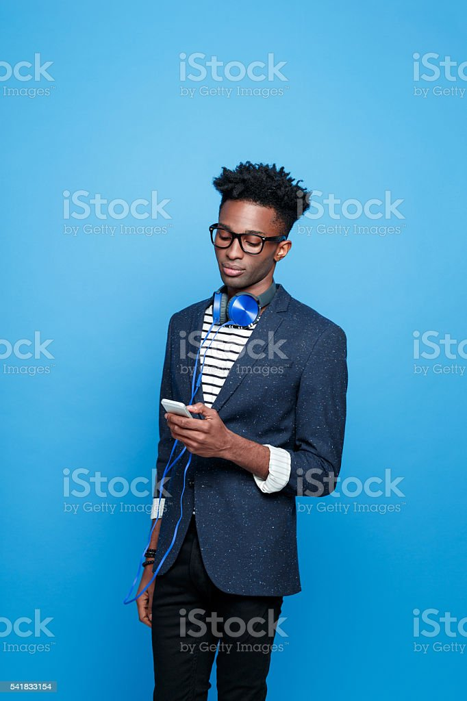Afro american guy in fashionable outfit using smart phone Fashionable afro american young man wearing striped top, navy blue jacket, nerd glasses and headphone, using a smart phone. Studio portrait, blue background. Adult Stock Photo
